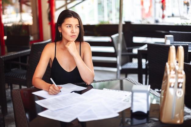 Zadumany młodej dziewczyny biznesowej kobiety studencki obsiadanie w kawiarni na ulicie z dokumentami na stole.