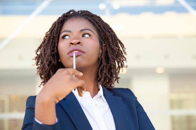 Zadumany młody bizneswomanu mienia pióro