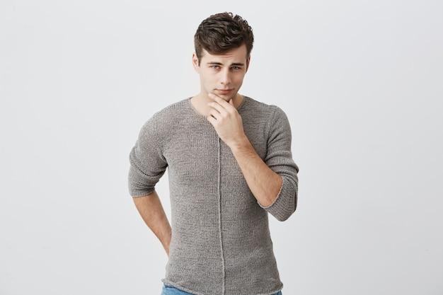 Zadumany młody caucasian facet jest ubranym sweter dotyka jego podbródek i patrzeje naprzód z słabym uśmiechem. przystojny przystojny mężczyzna o niebieskich oczach. ludzkie uczucia i wyraz twarzy.
