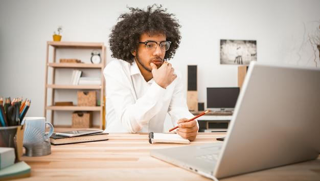 Zadumany młody człowiek jest zaręczony w domu przed komputerem.