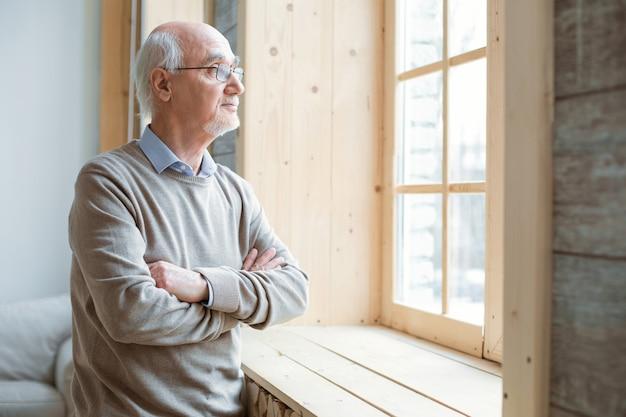 Zadumany nastrój. przemyślany atrakcyjny starszy mężczyzna patrząc przez okno podczas krzyżowania rąk i pobytu