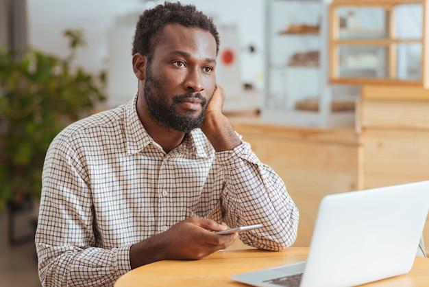 Zadumany nastrój. przystojny młody mężczyzna siedzi w kawiarni, trzymając telefon i wpatrując się w dal, zastanawiając się nad wiadomością tekstową i zdenerwowany