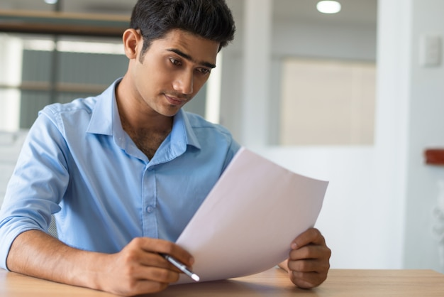 Zadumany skoncentrowany indiański prawnik egzamininuje papier