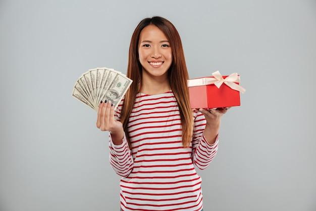Zadziwiająca emocjonalna młoda azjatykcia dama trzyma prezent i pieniądze.