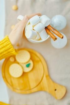 Zadziwiająca kobieta pije gorącego cacao z marsmallows i cynamonem w żółtym pulowerze