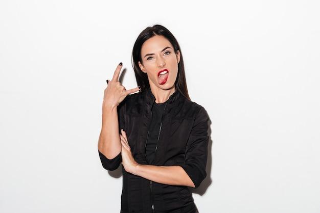 Zadziwiająca kobieta z czerwonymi wargami pokazuje język i rockowego gest.