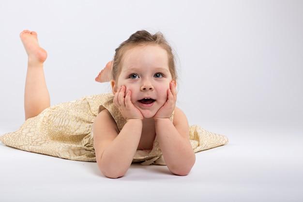 Zadziwiająca mała dziewczynka w sukni siedzi na żółtej podłoga