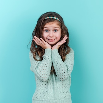 Zadziwiająca małej dziewczynki pozycja na błękitnym tle
