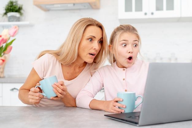 Zadziwiająca matka i córka patrzeje na laptopie