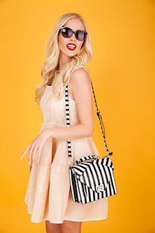 Zadziwiająca potomstwo mody blondynki kobieta jest ubranym okulary przeciwsłonecznych.