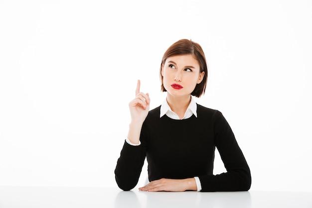 Zadziwiająca poważna młoda biznesowa kobieta wskazuje up z palcem