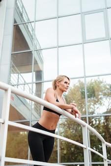 Zadziwiająca silna młoda sportowa dama stoi na zewnątrz