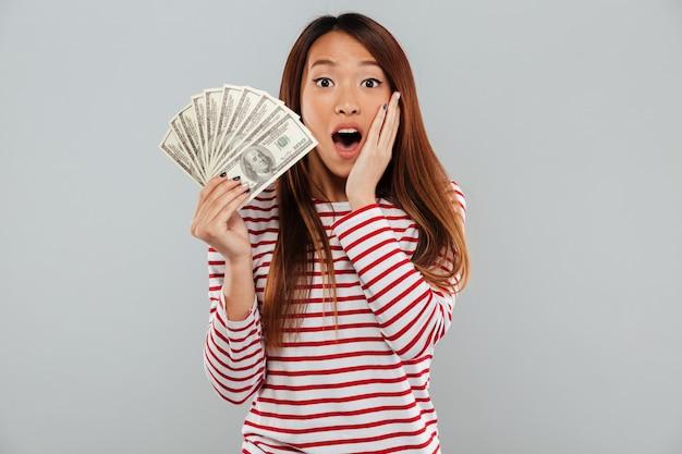 Zadziwiająca zszokowana młoda azjatykcia dama trzyma pieniądze.