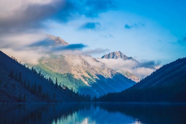 Zadziwiające niebieskie sylwetek góry pod błękitnym chmurnym niebem. piękne fale na wodzie górskiego jeziora. niskie chmury przed grzbietem górskim. cudowny krajobraz górski. malowniczy górski krajobraz.