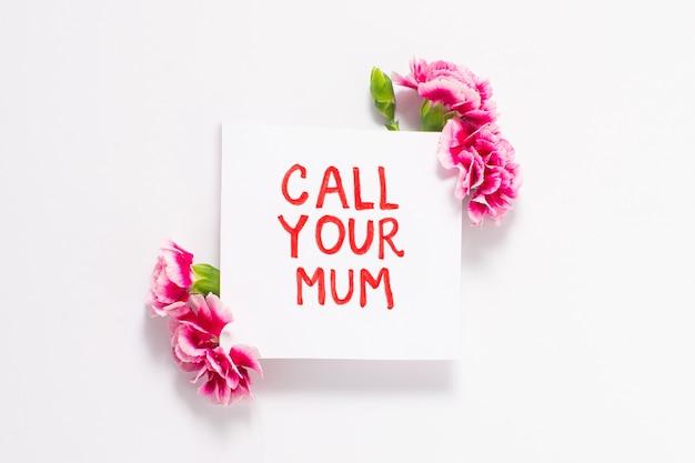 Zadzwoń do mamy na białym papierze z różowymi kwiatami na białym tle