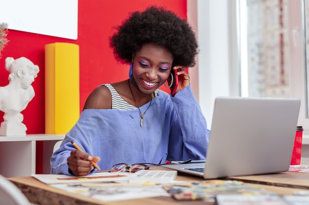 Zadzwoń od chłopaka. atrakcyjna stylowa młoda kobieta uśmiechnięta odbiera telefon od opiekuńczego kochającego chłopaka