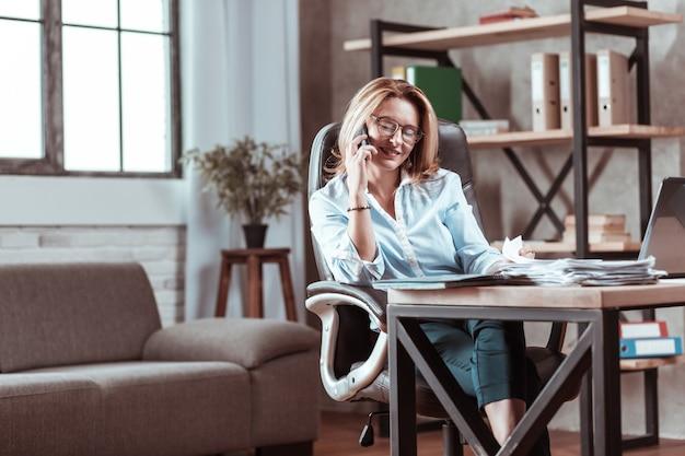 Zadzwoń od męża. piękna bizneswoman czuje się zadowolona i dobrze odbiera telefon od męża