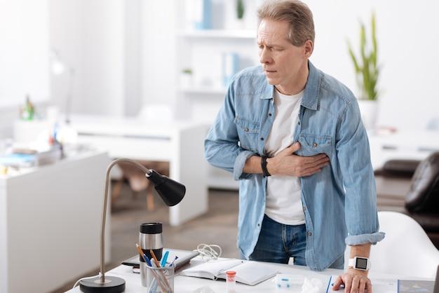 Zadzwoń po pomoc. nieaktywny mężczyzna stojący za swoim miejscem pracy kładąc lewą rękę na stole, dotykając jednocześnie swojego serca