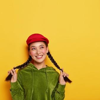 Zafascynowana, delikatna, młoda koreanka pokazuje długie warkocze, ma marzycielski zamyślony wyraz, ubrana w stylowe, jaskrawe ubrania