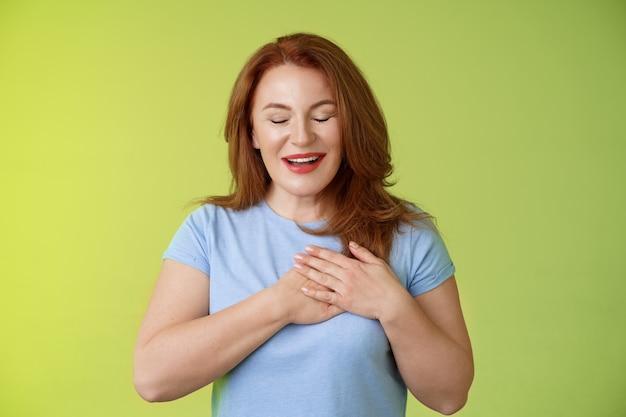 Zafascynowana śliczna ruda namiętna kobieta w średnim wieku wzdychająca uroczy dotyk serce zamknięte oczy uśmiechnięty zachwycony wyrazić podziw pokusa uczucie wdzięczności wdzięczność emocje zielona ściana