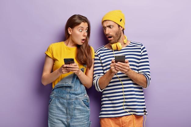 Zafascynowana, zdziwiona kobieta i mężczyzna ignorują prawdziwą komunikację, boją się złego połączenia internetowego, nie mogą znaleźć odpowiedzi na egzaminie