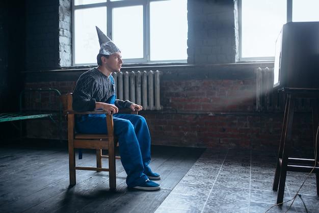 Zafascynowany mężczyzna w kasku z folii aluminiowej siedzi na krześle i ogląda telewizję, koncepcja paranoi. ufo, teoria spiskowa, ochrona przed kradzieżą mózgu, fobia