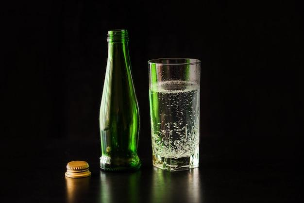 Zagazowana woda w szkle na czarnym stole i czarnym tle.