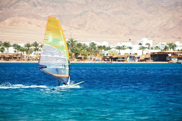 Żagiel windsurfingowy na błękitnym morzu przeciw wybrzeżu