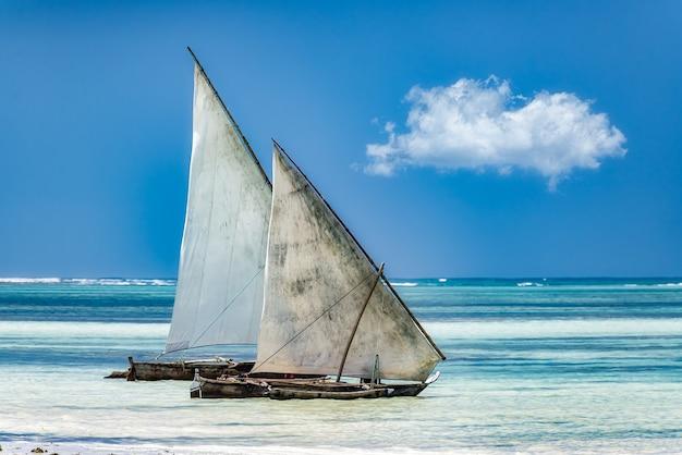 Żagle na morzu pod słońcem i błękitnym niebem