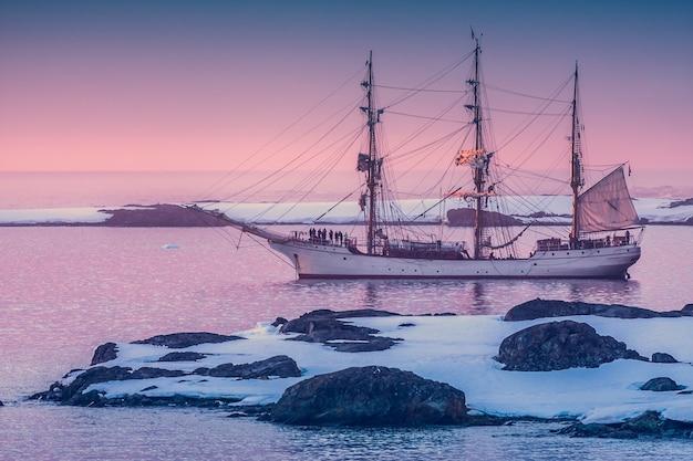 Żaglowiec na antarktydzie o świcie wśród gór lodowych