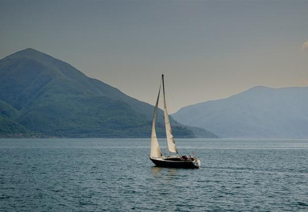 Żaglowiec pośrodku spokojnego morza przy zdobionych w szwajcarii wzgórzach