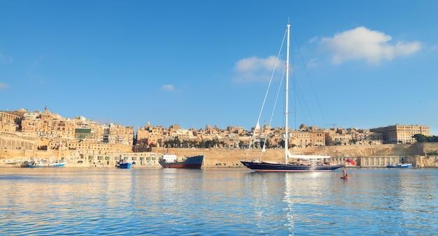 Żaglowiec wpływa do zatoki grand valetta w jasny dzień, panorama