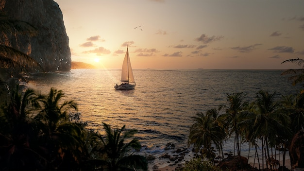 Żaglówka (łódź) na morzu w pięknym krajobrazie o zachodzie słońca z górami, ptakami i palmami kokosowymi - koncepcja wakacji, spokoju i przygody