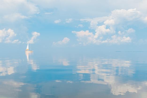 Żaglówka na morzu w słoneczny dzień na bajkowy malowniczy krajobraz z chmurami odbicie w wodzie.