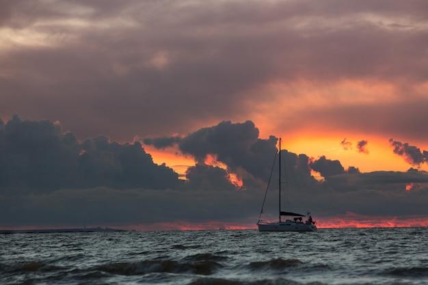 Żaglówka podczas zachodu słońca na tropikalnym morzu, dramatyczne niebo w tle. rejs i jacht