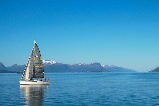 Żaglówki żeglarskie, błękitne niebo pochmurne i białe żagle molde norwegia, europa