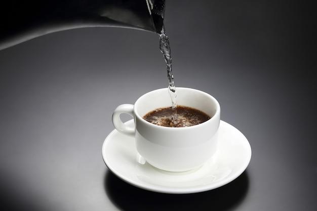 Zagotowaną wodę wlewa się do białej filiżanki z czarną kawą. gorący napój