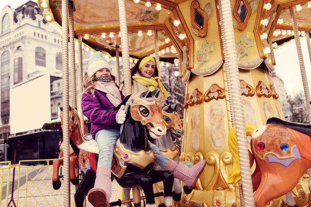 Zagrajmy. zadowolona dziewczyna siedzi na sztucznym koniu i patrząc na kamery