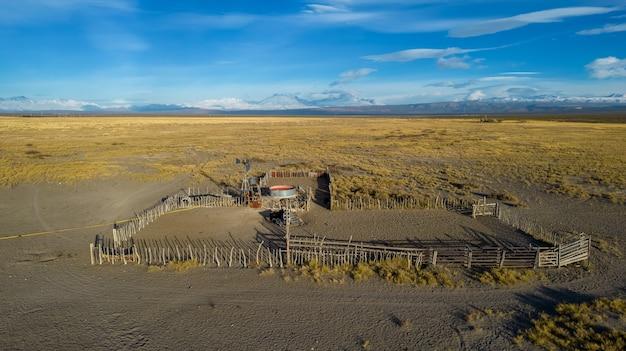 Zagroda dla zwierząt w patagonia argentyna, z młynem wodnym i górami w tle.