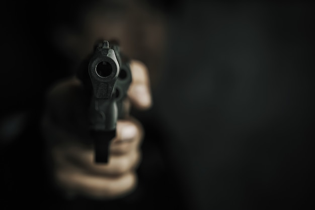 Zagrożenie bronią palną kaganiec pistoletu w dłoni mężczyzny jest wycelowany w kamerę mężczyzna przestępca trzyma rewolwer na b...