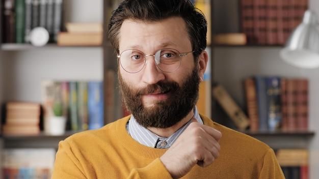 Zagrożenie. przekonany, brodaty mężczyzna w okularach w pokoju biurowym lub mieszkalnym, patrząc na kamery i biegnie grozi palcem wzdłuż jego szyi. zamknąć widok