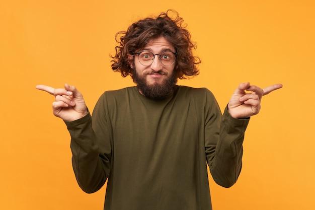 Zagubiony w dokonywaniu wyboru, brodaty mężczyzna z kręconymi włosami w okularach, wskazujący palcami wskazującymi po obu stronach