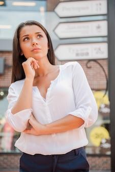 Zagubiony w mieście. rozważna młoda kobieta stojąca w pobliżu znaku kierunkowego i trzymająca rękę na brodzie