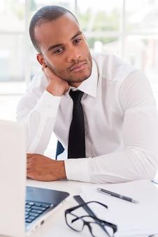 Zagubiony w myślach biznesowych. rozważny młody afrykanin w koszuli i krawacie, opierając głowę na dłoni