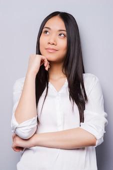 Zagubiony w myślach. rozważna młoda azjatka trzymająca rękę na brodzie i odwracająca wzrok, stojąc na szarym tle