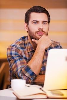 Zagubiony w myślach. rozważny młody mężczyzna trzymający rękę na brodzie i odwracający wzrok, siedząc w kawiarni