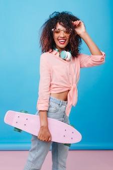 Zainspirowana afrykańska modelka w żółtych okularach przeciwsłonecznych, dobra zabawa. uśmiechnięta dziewczyna mulat z deskorolka, pozowanie w pokoju z niebieskim wnętrzem.