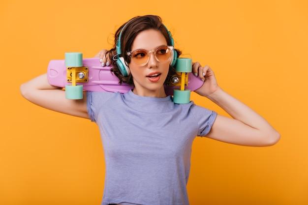 Zainspirowana biała dziewczyna w eleganckich okularach przeciwsłonecznych z kolorowym longboardem. wewnętrzne zdjęcie zainteresowanej modelki w dużych modnych słuchawkach.