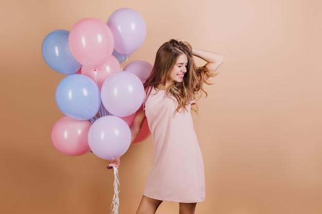 Zainspirowana biała kobieta o ciemnych włosach śmiejąca się podczas pozowania z balonami