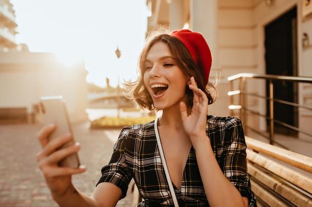 Zainspirowana biała kobieta z krótką fryzurą, która bawi się w jesienny dzień. zewnętrzne zdjęcie fascynującej francuskiej modelki w berecie trzymającej smartfon.